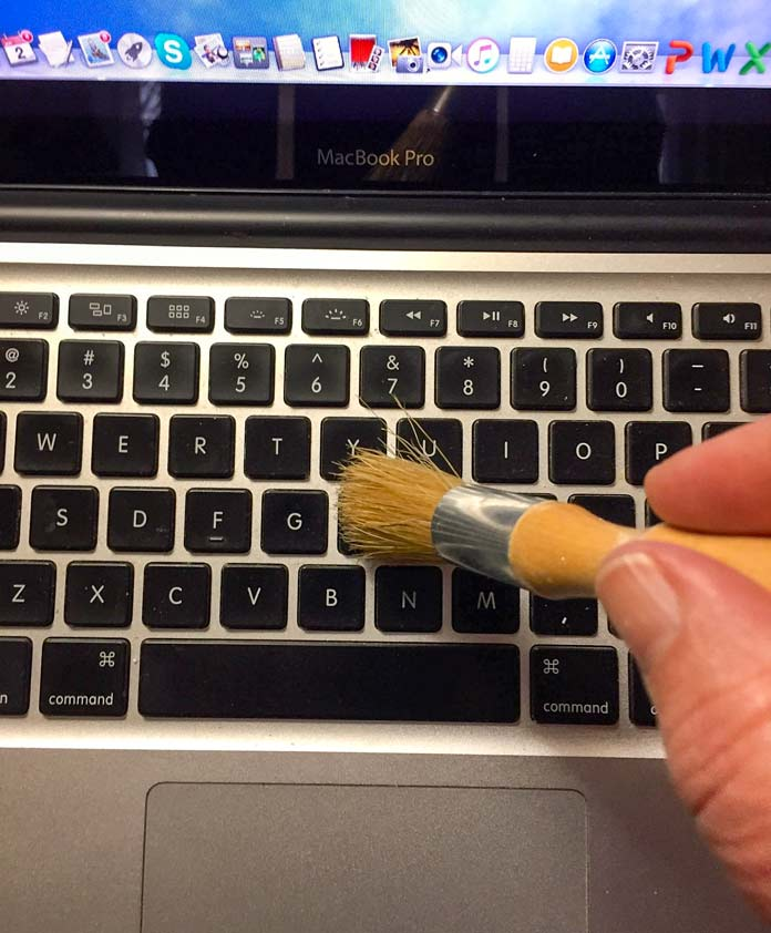 Using my UNIQUE longarm quilters' dust brush to clean between the keys of my laptop.