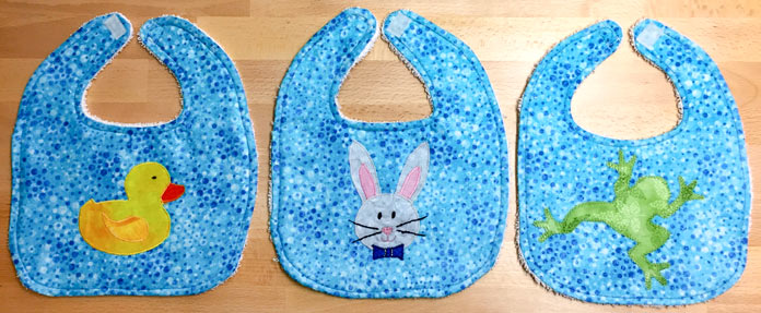 Baby bibs using HeatnBond Feather Lite and Pressing Paper, fabric from Northcott Stonehenge Kids Undersea 3D.