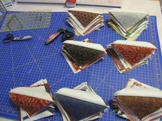 Half Square Triangles on a Unique cutting mat to make a quilt