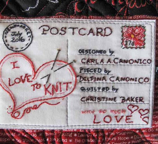 The finished quilt label on the red fabric of the I Love to Knit quilt