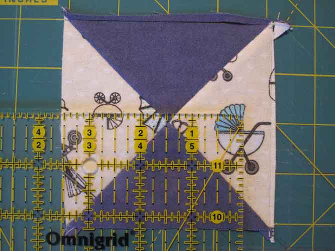 Placing the QST on the cutting mat makes it obvious that the block isn't a precise square and a precise square is what makes an impeccable quilt – at least an impeccable foundation.