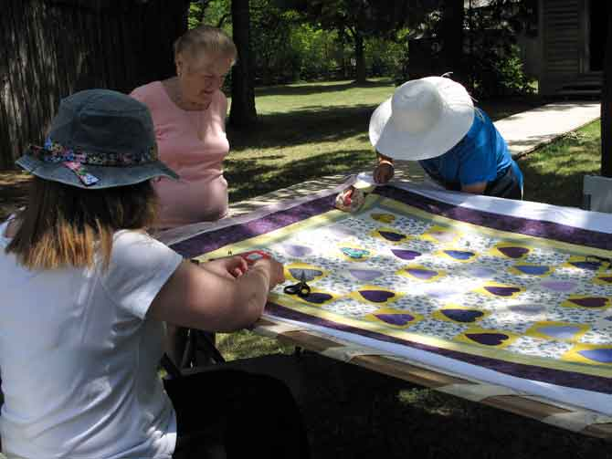 Quilters at work over a frame, and mom supervising them. : ))