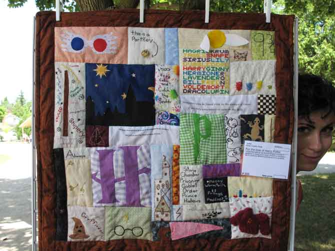 This is a fascinating concept where every block has a different form of needlework all unified on this quilt! That would be my daughter peeking from the right side of the quilt.