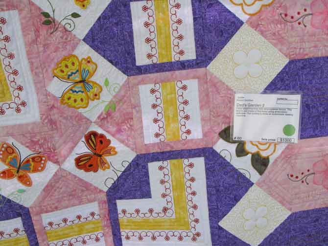 Great use of machine embroidery applied to the fabric before it's cut into squares and sewn into quilt blocks!