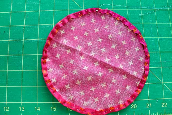 Create a more finished looking yo-yo by folding the fabric in and stitching through both layers around the circle.