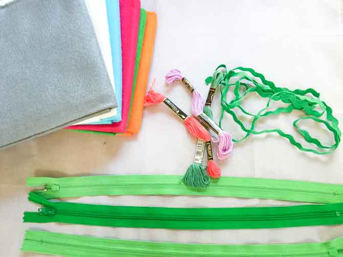 Materials for table runner including wool felt, DMC embroidery floss and green zippers.