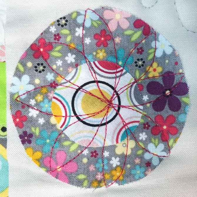 Free motion quilt a flower design in the circles.