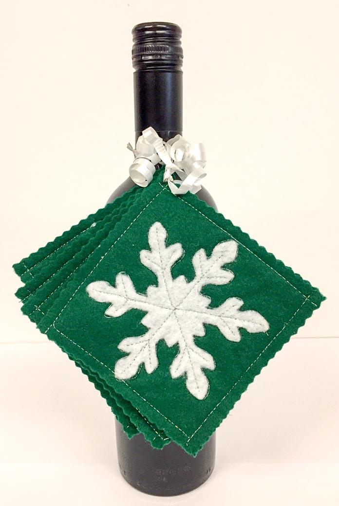 Snowflake coasters attached to a bottle of wine and ready for gift giving, Kunin Rainbow ClassicFelt (green and white), Sulky Holoshimmer and Hi-tak Glue