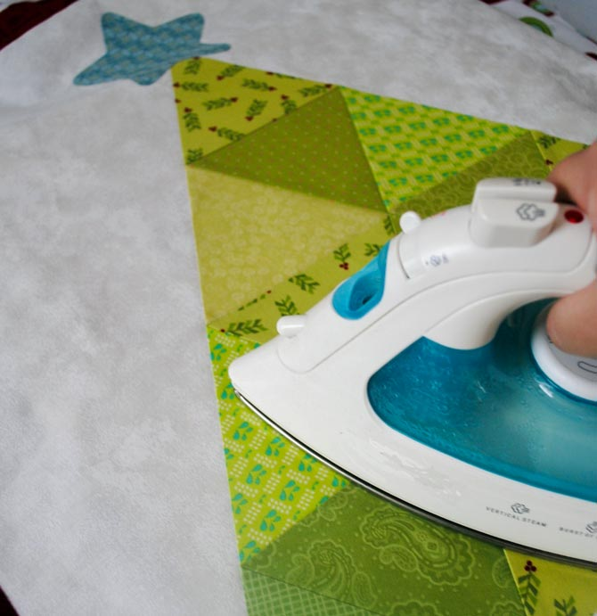 Ironing the applique to the quilt top
