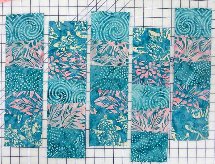"Use a rotary cutter to cut the strip set into 5 - 4"" segments; using Banyan Batiks Island Vibes fabrics to make a modern quilt, placemat, cushion cover etc."