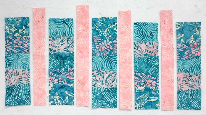 Arrange pink strips between the pieced segments in preparation for sewing; using Banyan Batiks Island Vibes fabrics to make a modern quilt, placemat, cushion cover etc.