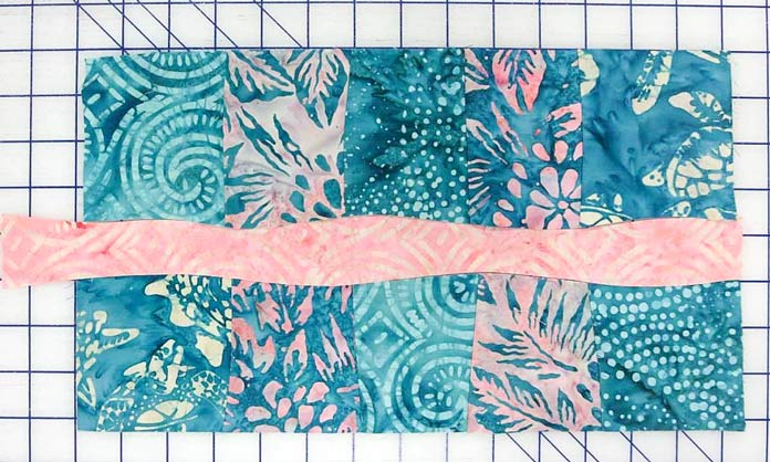 Sew the curvy pink strip to the pieced segments; using Banyan Batiks Island Vibes fabrics to make a modern quilt, placemat, cushion cover etc.