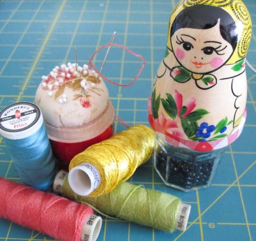 4 specialty threads by WonderFil and a Matryoska doll pin cushion with a jar of beads is a great start to making a mini quilt. See our free Studio Bird pattern.