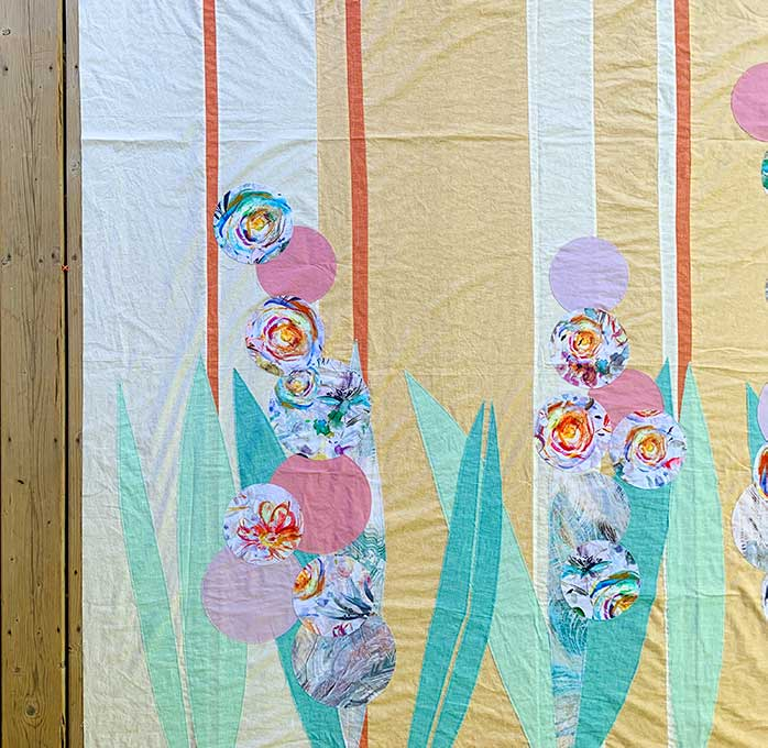 A picture of a quilt design featuring leaves and circles as flower stems