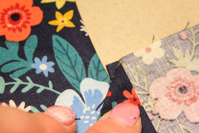 Press the seams towards the square, leaving seams stitch-free for the mitered corner.