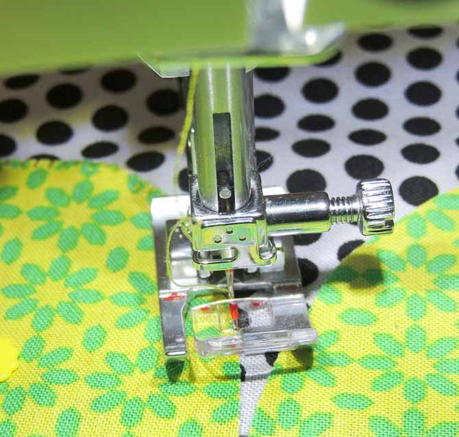 The center red guide lines up on the edge of the fabric to start machine blanket stitching on the passport 3.0.