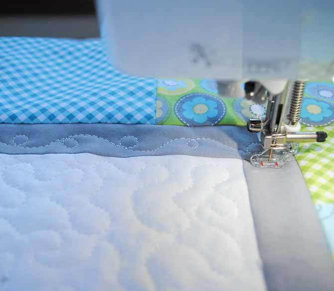 A loop design is machine stitched in the inner border of the baby quilt using the quilting foot on the Brother NQ900.