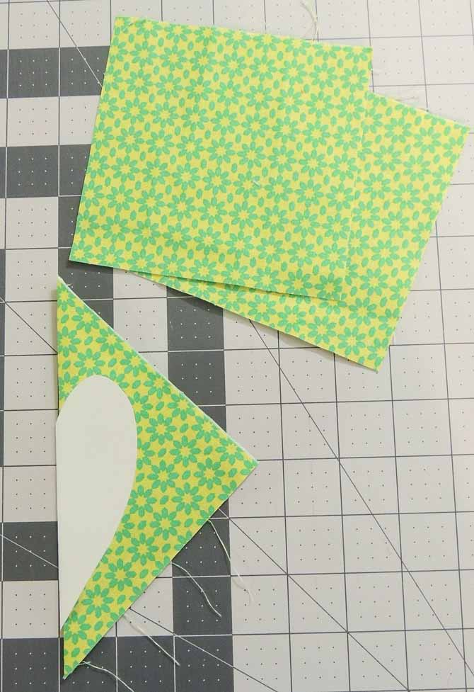 The green applique hearts are cut using the paper template.
