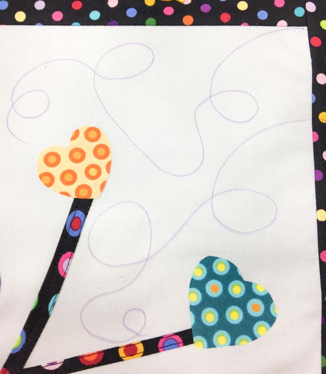 Marker swirls drawn on quilt top before quilting.