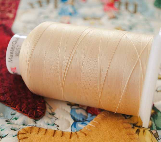 A cone of Master Quilter thread from WonderFil is displayed on a Christmas tablerunner.