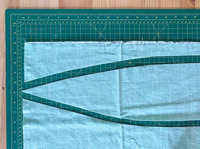 A picture showing green fabric being cut into improv leaf shapes for applique