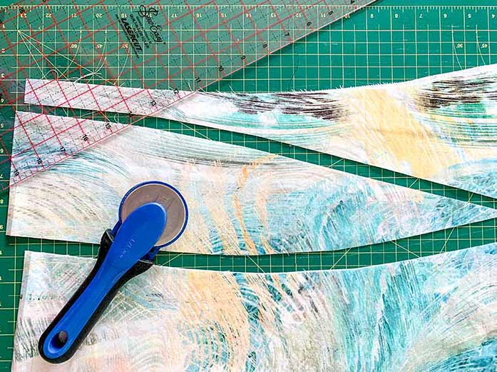 A picture showing a rotary mat, rotary cutter, ruler and quilting fabric