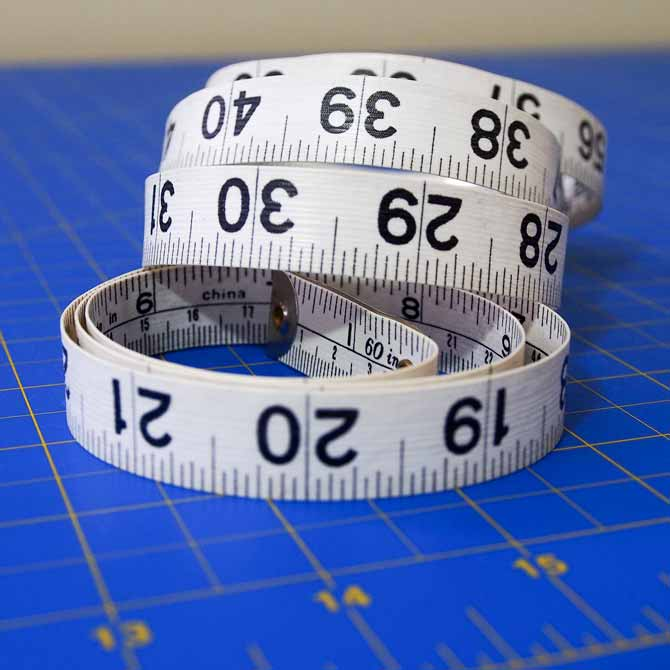 Curled up measuring tape on a blue cutting mat