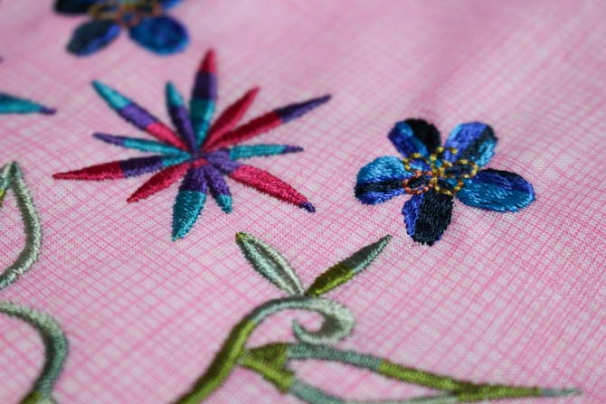 Blue and purple flowers which have been machine embroidered with WonderFil's Mirage rayon thread.