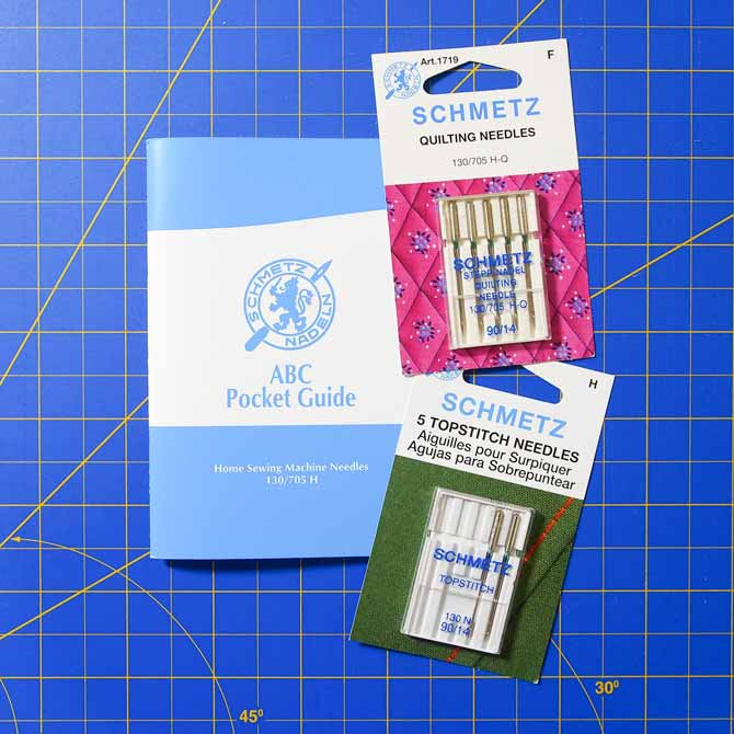 2 cards of Machine quilting needles and a book about machine sewing needles on a blue mat