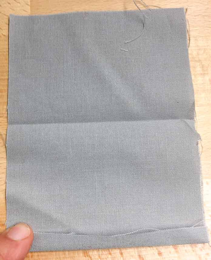 One edge of fabric pressed under ¼""