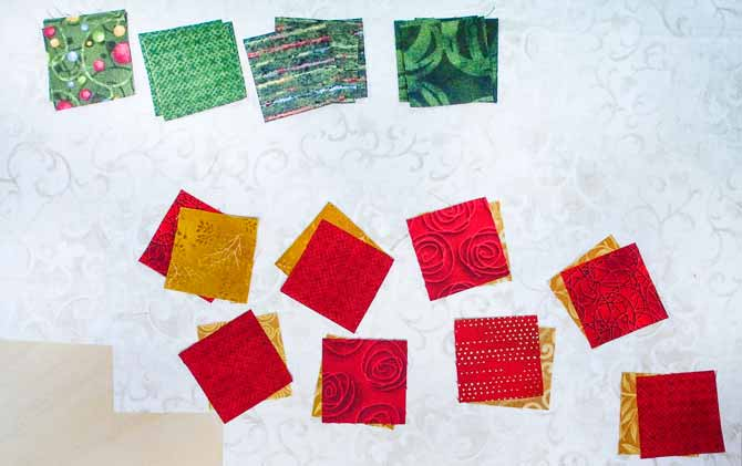 red, gold and green squares on cream fabric with the red and gold squares paired up together