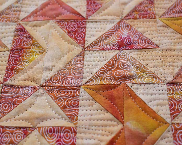 InvisaFil is 100wt cottonized polyester. It's perfect for fine quilting stitches. For piecing, I used the 80wt DecoBob thread.