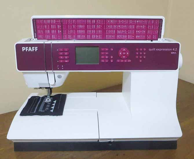PFAFF Quilt Expression™ 4.2 machine with flip lid showing decorative stitches