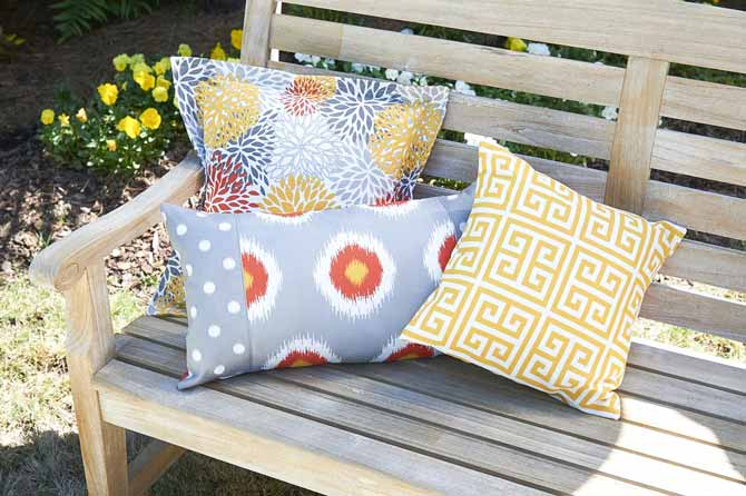 3 patio cushions in bright colored fabrics on a bench made using Coats Outdoor Thread