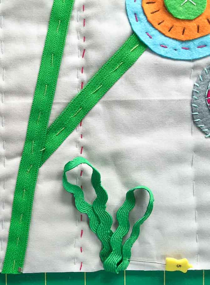Loop rick rack at bottom of quilt to create grass. Pin and then tack down.