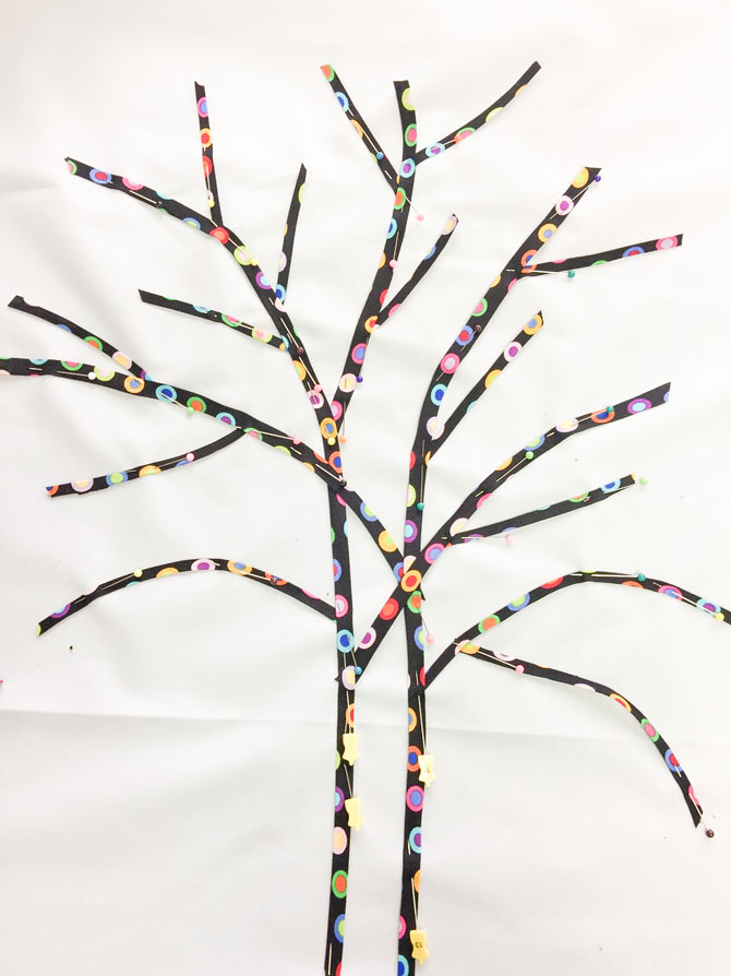 Bias tape laid out on background in the shape of a tree with branches and pinned down.