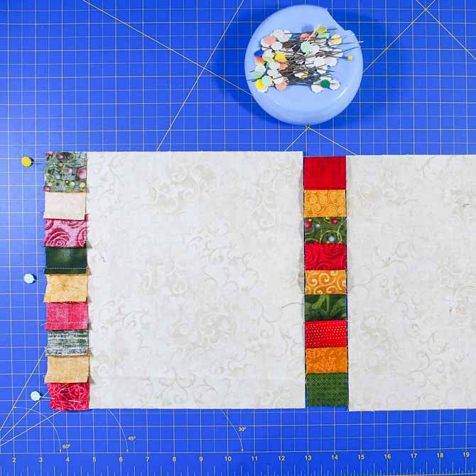 Sashing pinned to a cream square with flower headed pins sitting in a blue magnetic pin holder on a blue cutting mat
