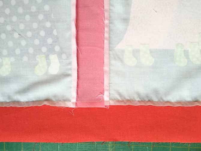 The wrong side of the quilt top is shown with the fabric being pressed to the dark fabric.