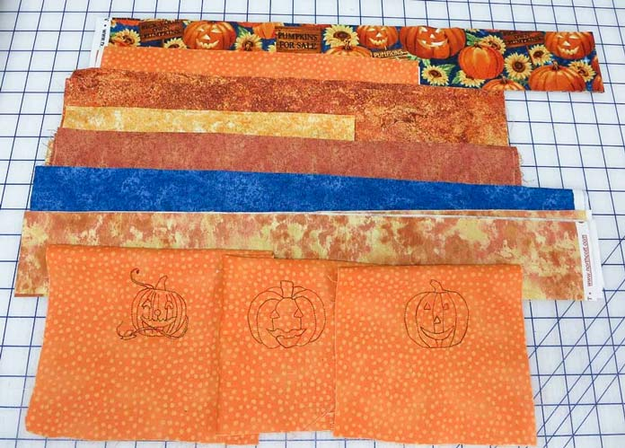 Embroidered pumpkins and coordinating fabrics for a Halloween wallhanging