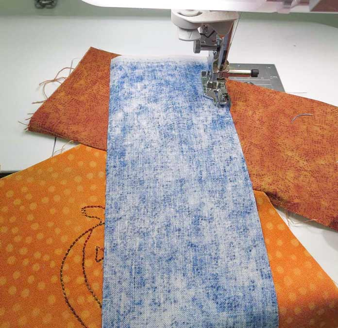 "Sew another 3"" strip on the embroidered square."