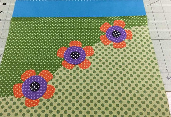 The wonderful flower appliques made with Northcott's Urban Elementz Basix fabrics are positioned on the ends of the spring table runner.