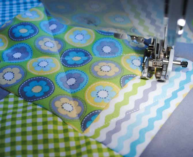 The walking foot on the Brother NQ900 is used to quilt diagonal lines across the squares in the border of the baby quilt.