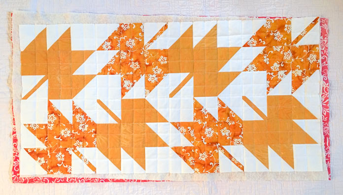 A background of beautiful maple leaves and simple grid quilting