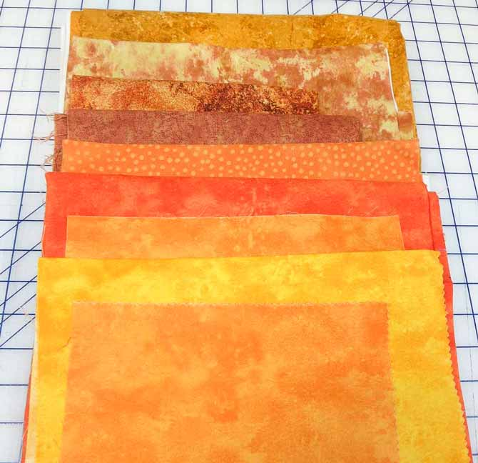 Orange fabrics for the sky in my improv wonky houses