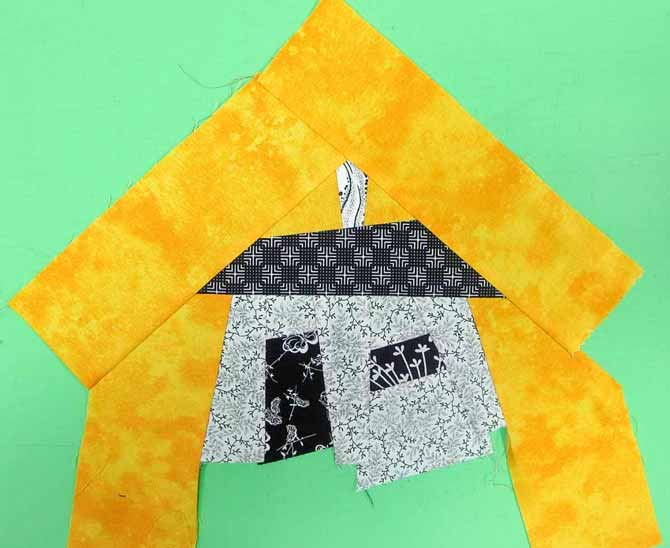 Sew a piece of sky fabric to each side of the roof.