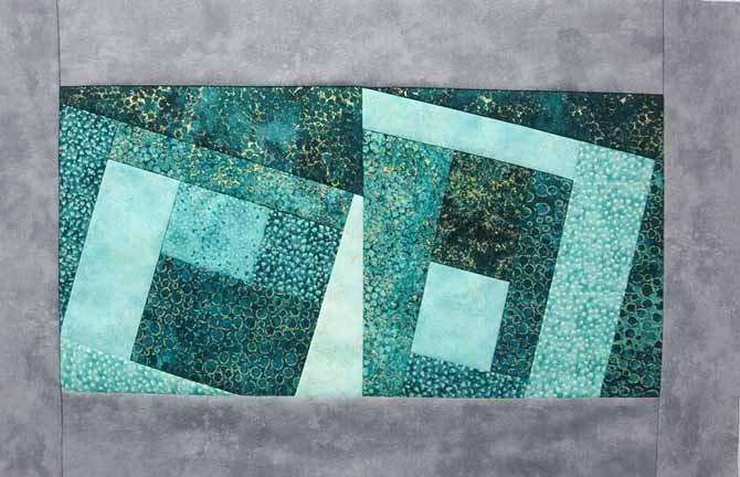 Two modern Log Cabin blocks made with Northcott's Artisan Spirit Shimmer fabrics are sewn together with a gray Toscana border to make a placemat.
