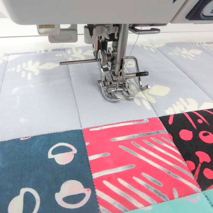 Using a quilting guide attached to the walking foot