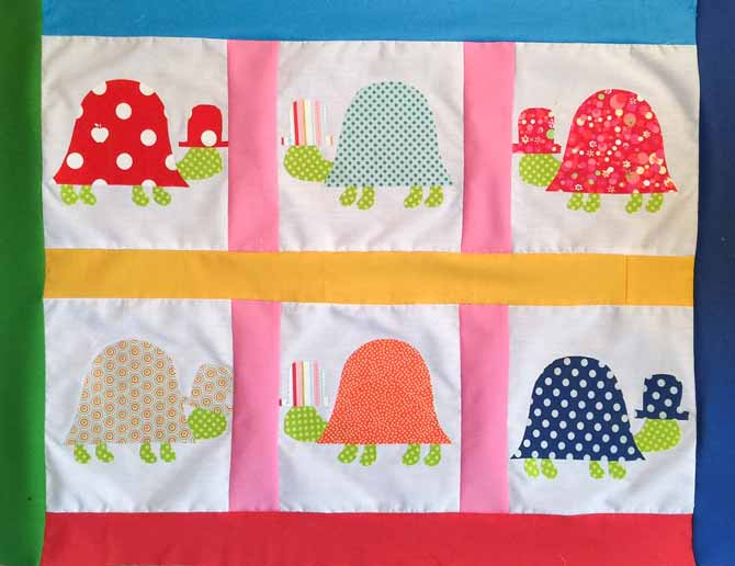 Quilt top with fused fabric turtles on a white background with various colors for sashing and border.