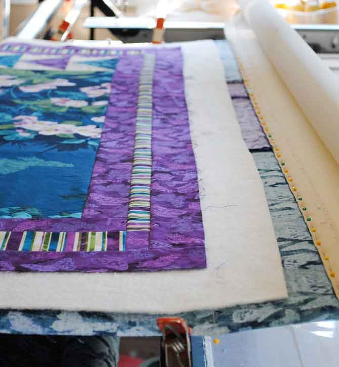 Quilt top and batting on top of the backing and clamps on the sides