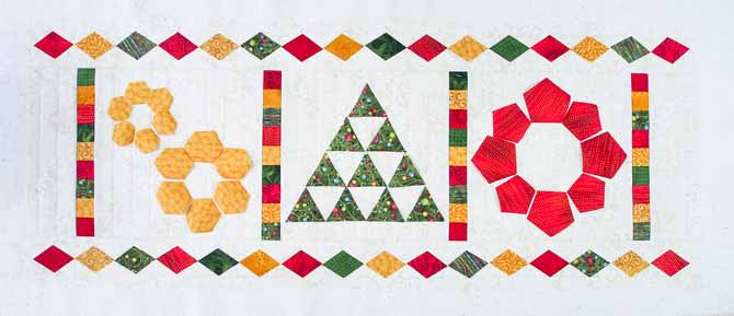 Cream colored runner with red, green & gold applique shapes in the form of diamonds, snowflakes, tree and wreath